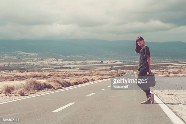 young woman with suitcase hitchhiking on road - atlantic islands stock photos and pictures