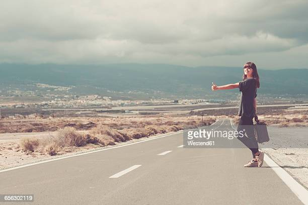 young woman with suitcase hitchhiking on road - hitchhiking stock pictures, royalty-free photos & images