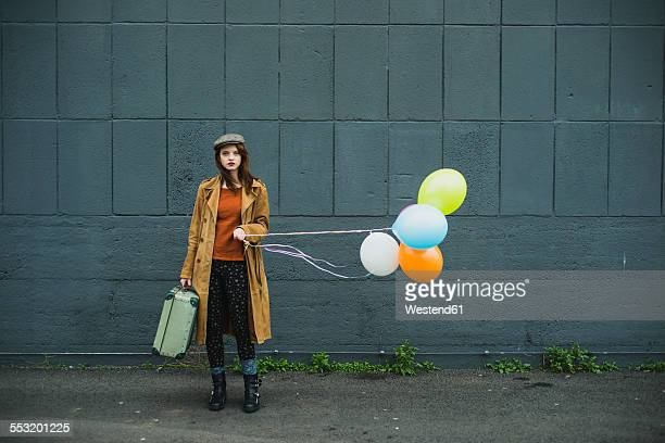 Young woman with suitcase holding bunch of balloons