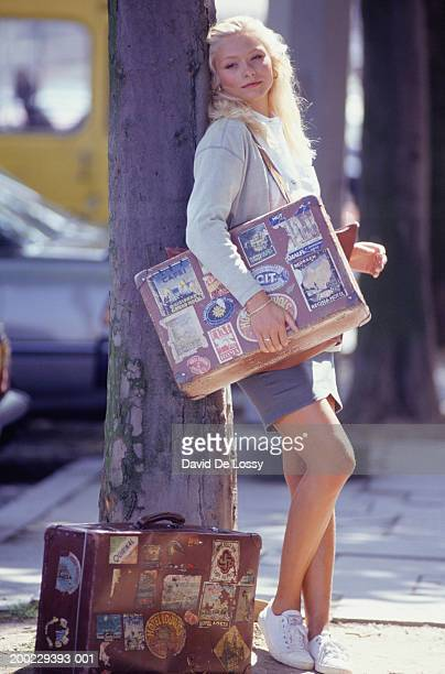 Young woman with suitcase leaning against tree trunk, portrait