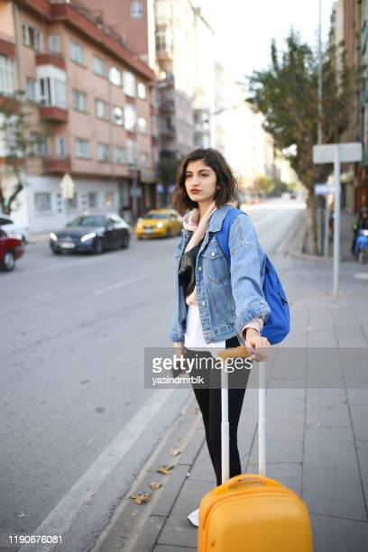 young woman with suitcase waiting for taxi - cashmere stock pictures, royalty-free photos & images