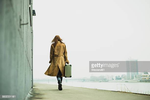 young woman with suitcase walking by the riverside - abschied stock-fotos und bilder