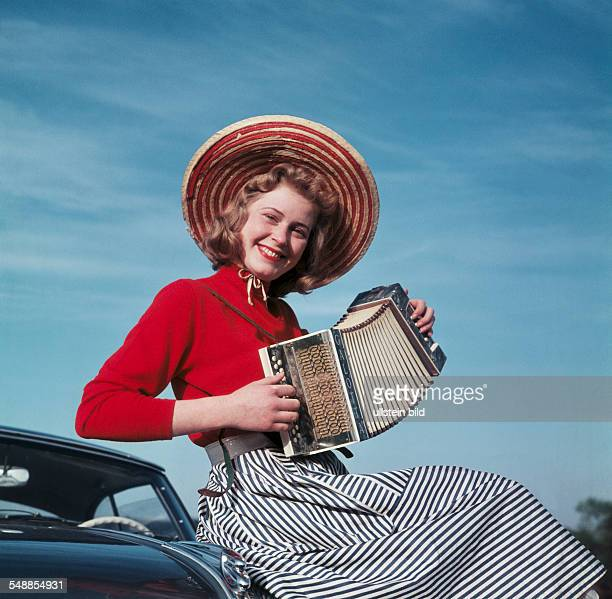 young woman with sun hat is playing the accordion 1950s