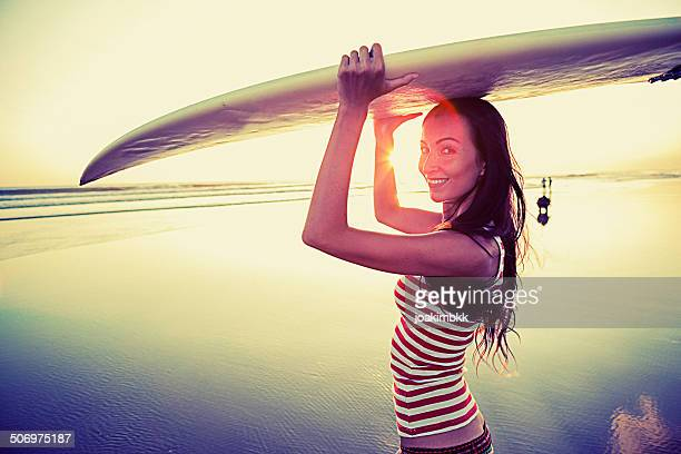 Young woman with surf board on the beach