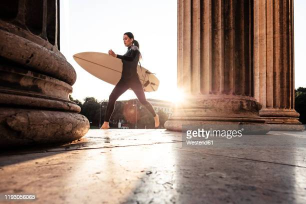 young woman with surfboard on the way to eisbach, munich, germany - münchen stock-fotos und bilder