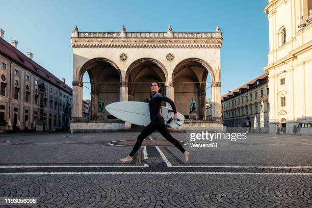 young woman with surfboard on the way to eisbach, munich, germany - scalzo foto e immagini stock