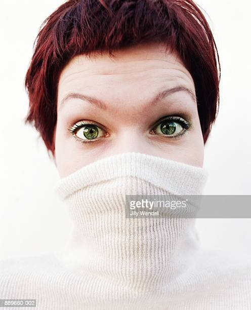 young woman with sweater neck over nose and mouth - high collar stock pictures, royalty-free photos & images