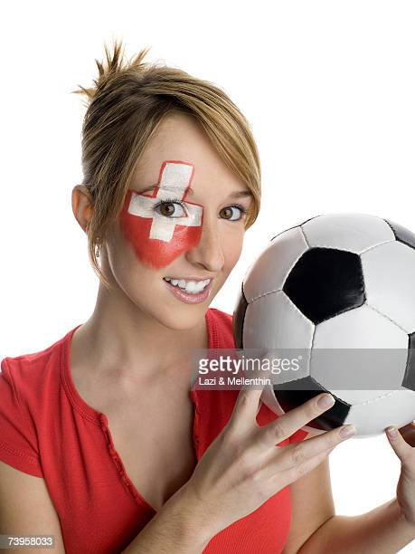 Woman with Swiss flag painted on face, holding football, smiling, portrait