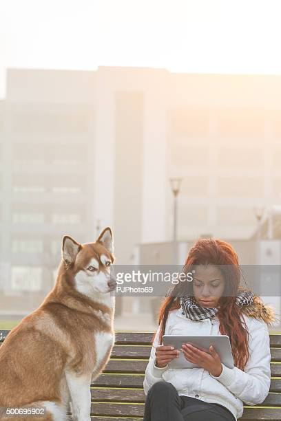 Young woman with tablet and her dog