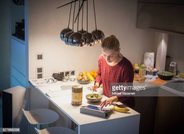 Young woman with tablet having breakfast