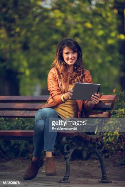 Jeune femme avec une tablette dans le parc