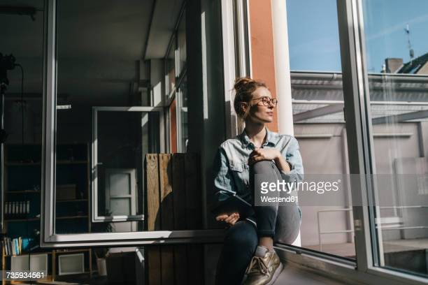 young woman with tablet looking out of window - looking at view stock-fotos und bilder