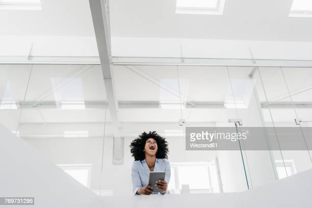 young woman with tablet screaming in office - aufregung stock-fotos und bilder
