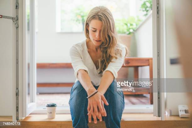 young woman with takeaway coffee sitting at balcony - guardare verso il basso foto e immagini stock