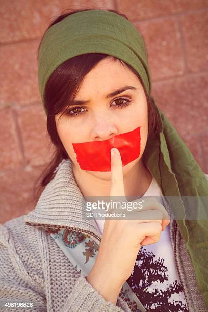 Young woman with tape and finger over her mouth
