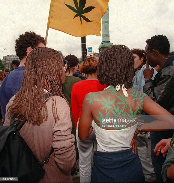 Young woman with tatoos of cannabis leaves covering her back participates 07 June in a street protest rally in Paris where about one thousand people...