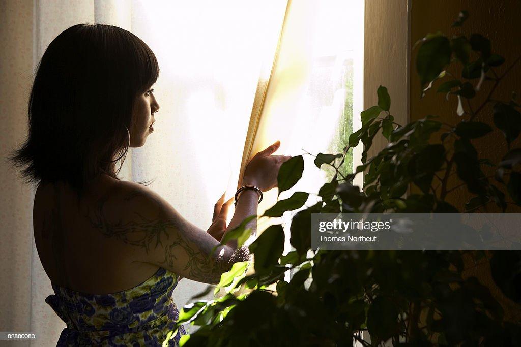 Jeune femme avec tatouage regardant par la fenêtre : Photo