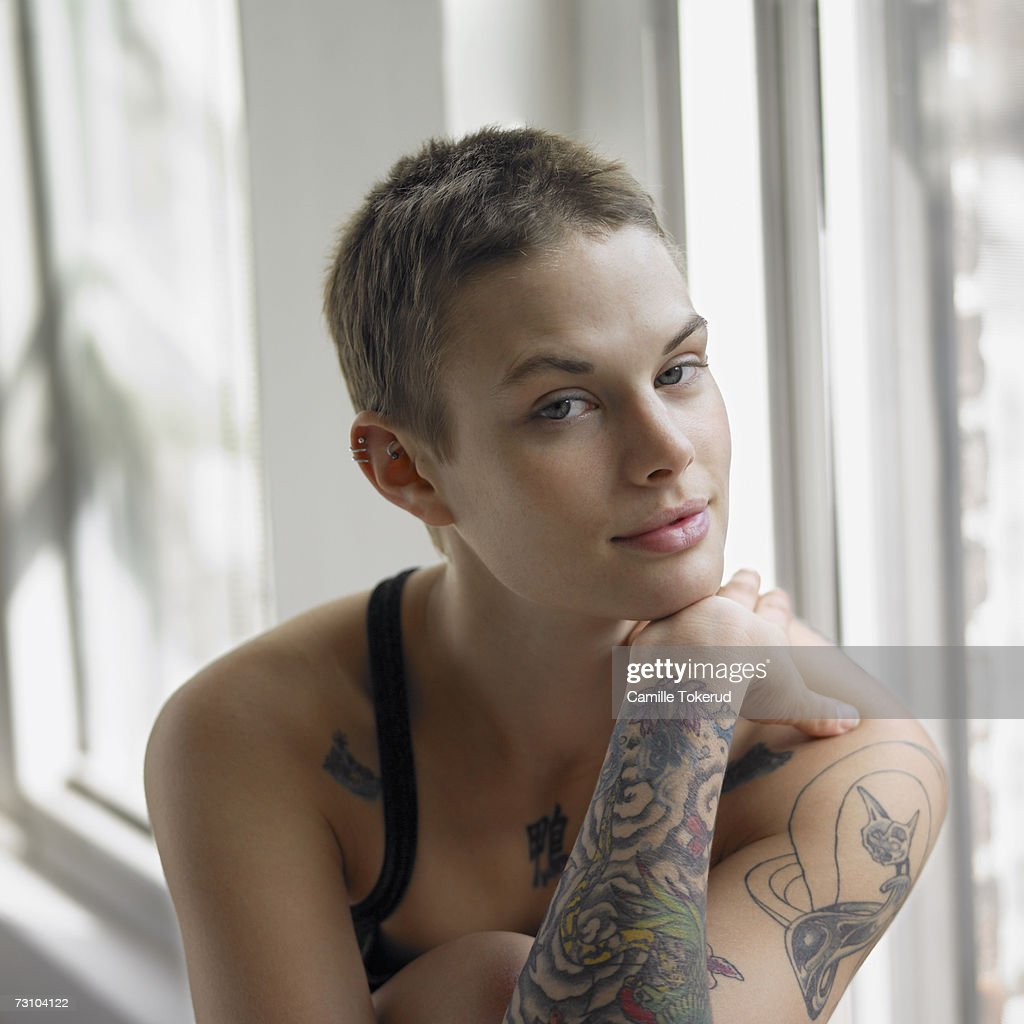 Young woman with tattoo on hand, portrait : Stock Photo