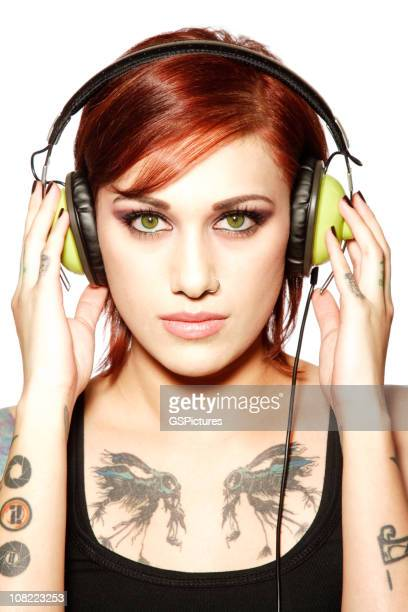 Young Woman With Tattoos Listening to Headphones