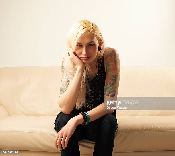 Young woman with tattoos sitting on sofa.