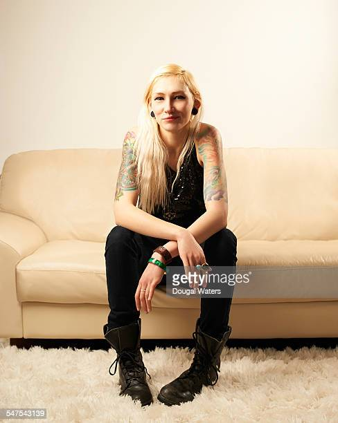 Young woman with tattoos smiling on sofa.