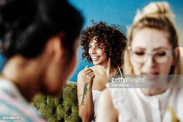 Young Woman With Tattoos Smiling While Chatting To Friends