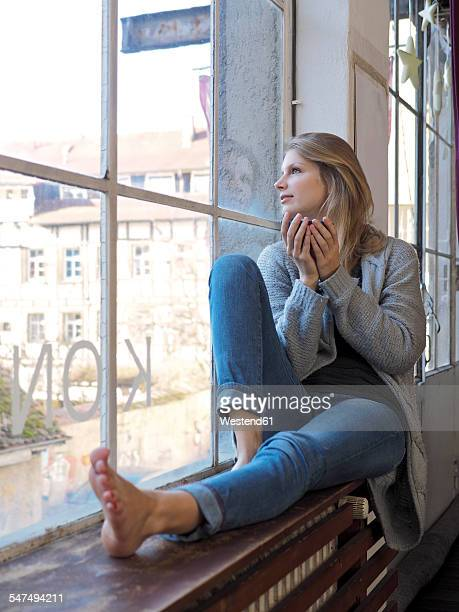 Young woman with tea bowl sitting on window sill