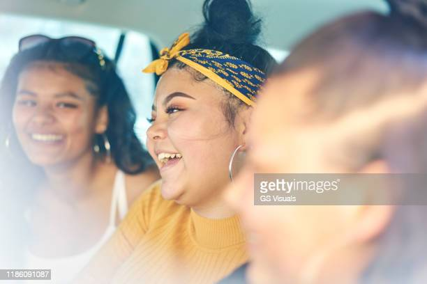 young woman with teenage sisters in car back seat laughing, close up - teenager stock pictures, royalty-free photos & images