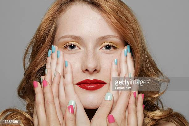 Young woman with three sets of hands touching her cheeks
