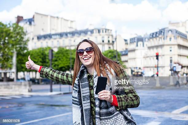 Young woman with thumb up for hitch-hiking at Chapms Elysees