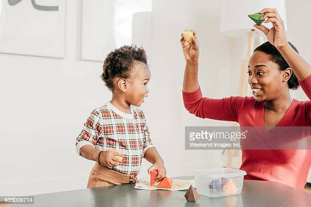 Young woman with toddler playing with toys