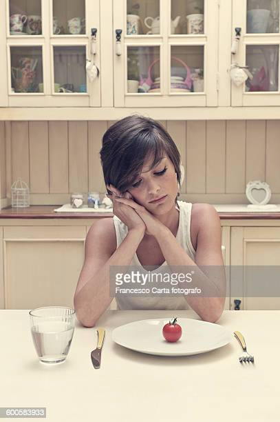 young woman with tomato on a plate - anorexia nervosa imagens e fotografias de stock