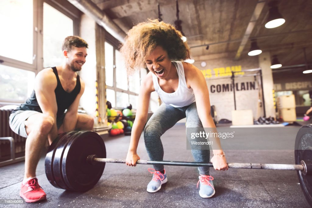 Young woman with training partner preparing to lift barbell in gym : Stock Photo