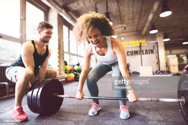 young woman with training partner preparing to lift barbell in gym - sports training stock pictures, royalty-free photos & images
