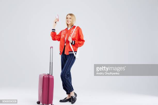 young woman with travel bag holding passport and boarding pass. - ラケット ストックフォトと画像