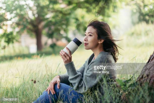 young woman with travel mug sitting in meadow - contemplation stock pictures, royalty-free photos & images