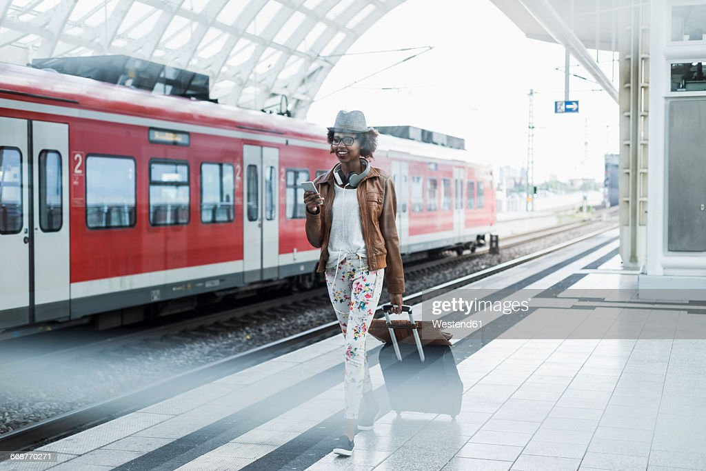 Young woman with trolley bag and smartphone at platform : Stock-Foto