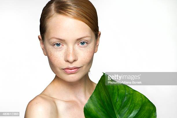Young woman with tropical plant leaf, portrait