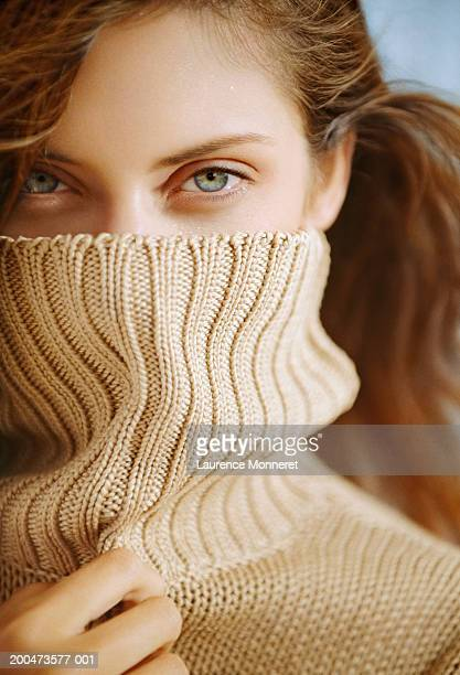 young woman with turtleneck over face, smiling, close-up, portrait - turtleneck stock pictures, royalty-free photos & images