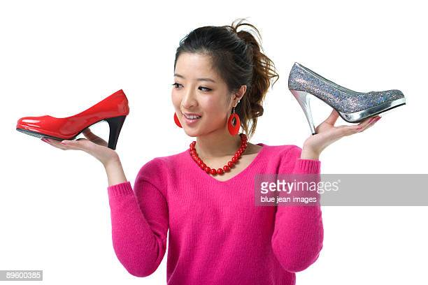 Young woman with two high-heeled shoes