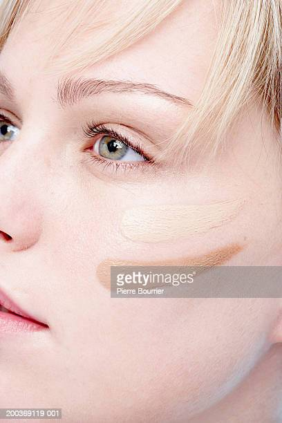Young woman with two shades of foundation on cheek, close-up