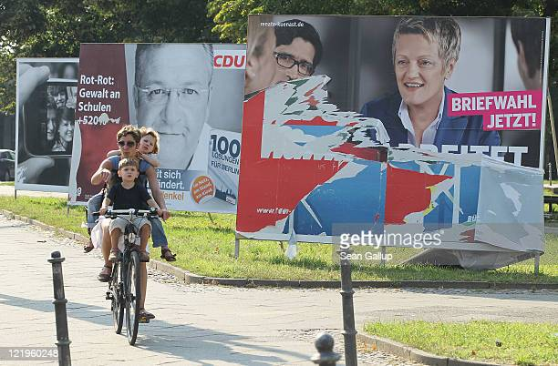 A young woman with two small children rides a bicycle past election campaign billboards including one picturing German Greens Party lead candidate...