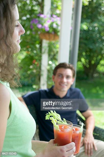 young woman with two tomato drinks, man in background - bloody mary stock photos and pictures