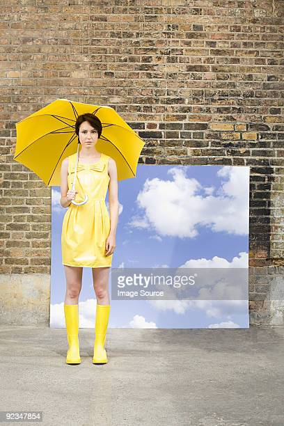 Young woman with umbrella and sky background
