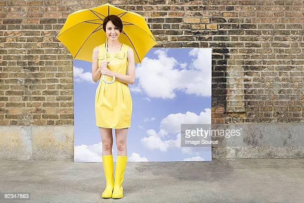 young woman with umbrella and sky background - yellow dress stock pictures, royalty-free photos & images