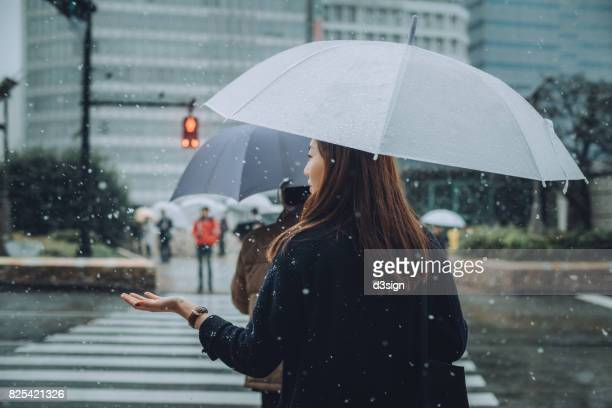 Young woman with umbrella enjoying the snowfall in city street