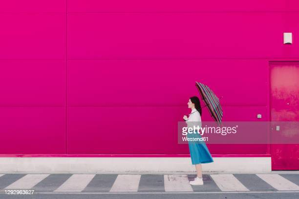young woman with umbrella in front of a pink wall - pink skirt stock pictures, royalty-free photos & images