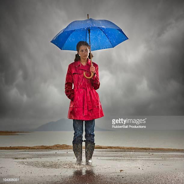 joven mujer con sombrilla jugar en charco - gabardina ropa impermeable fotografías e imágenes de stock