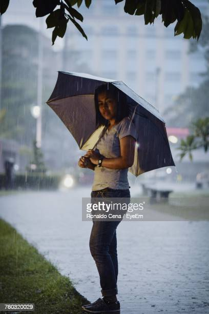 Young Woman With Umbrella Standing On Footpath During Rainy Season