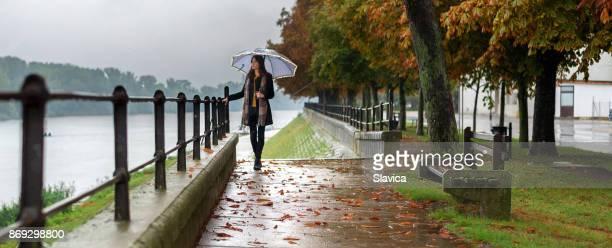 Junge Frau mit Regenschirm im Herbst Regen zu Fuß